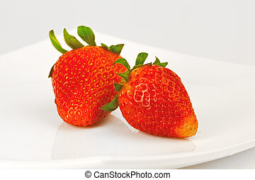 Two berries of strawberry on a whi
