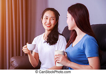 two best friends talking and drinking a cup of coffee on sofa at home