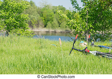 Two bicycles and a backpack are in the grass.