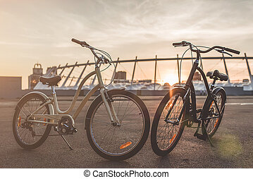Two bicycles in the city on the sunset