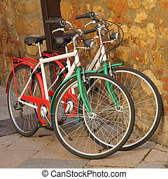 two bicycles painted in colors of Italy  against on stone wall o