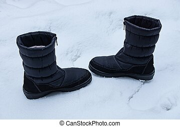 two big black boots of matter standing on white snow on the street