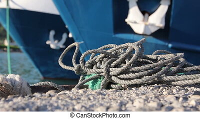 Two big fishing boats are tied up with rope for the dock, marina