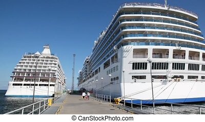 two big passenger liners stand in port on either side of mooring