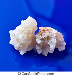 Two big peices of natural crystal of salt on a blue background with reflection.