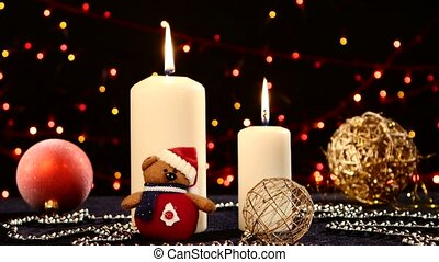 Two big white candles with balls and teddy for christmas on black, bokeh, light, garland, dynamic change of focus