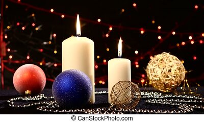 Two big white candles with balls for christmas on black, bokeh, light, garland