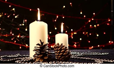 Two big white candles with pine cone for christmas on black, bokeh, light, garland