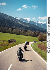 Two biker riding alone on mountainous road
