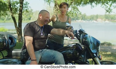 Two bikers communicating near motorcycle outdoors - Positive...