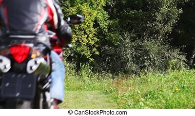 Two bikers on motorcycles goes forward on footpath in park