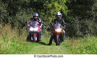 Two bikers on their motorcycles start on footpath together