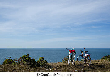 Two bikes by the coast - Two bikes with towels stands by the...