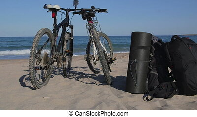 Two bikes with backpacks on the summer beach