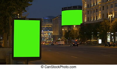 Two billboards with a green screen. In the evening, on a busy street.