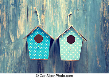 two birdhouses on antique rustic wood background.