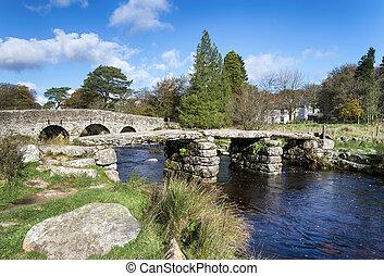 An ancient clapper bridge and arched bridge crossing the East Dart river at Post Bridge on Dartmoor