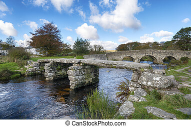 Two bridges, an ancient clapper bridge and arched bridge crossing the East Dart river at Post Bridge on Dartmoor