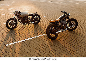 Two black and silver vintage custom motorcycles cafe racers