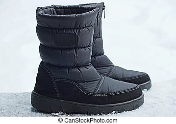 two  black boots of matter standing on white snow