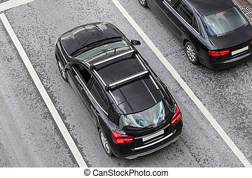 Two Black Cars on the road.