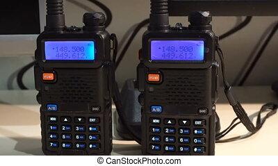 Two black handled portable walkie- talkie radio transmitter...