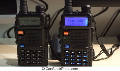 Two black handled portable walkie- talkie radio transmitter...