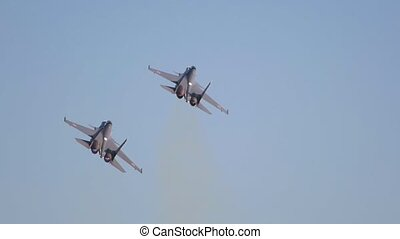 Two black military fighter jets flying in the sky. Mid shot