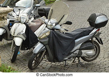 Two black motorcycles are parked on the street in Rome, Italy