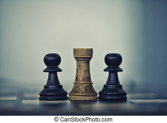 Two black pawns and a white rook on a chess board