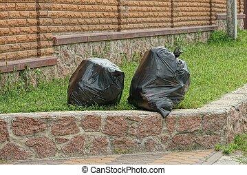 two black plastic bags full of rubbish