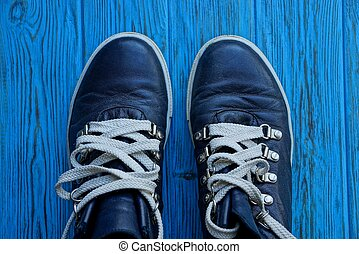 two black shoes with white laces on a blue board