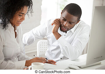 Two black workers discussing business ideas in office