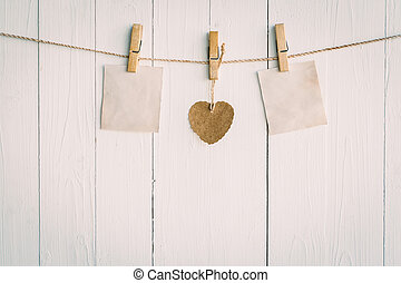Two blank old paper and brown heart hanging. On white wooden...
