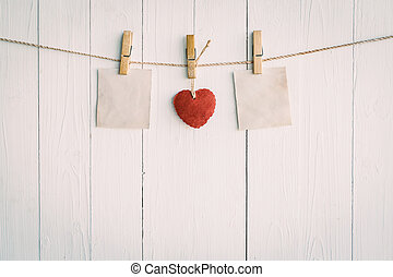 Two blank old paper and red heart hanging. On white wooden...
