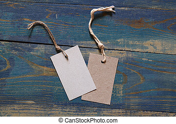 two blank price labels on blue wooden background