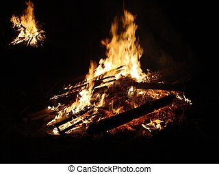 two blazing bon fires burning brightly in evening