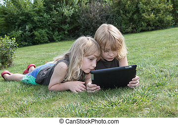 Two blond boys are looking to the tablet