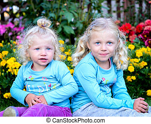 two blond girls sitting in the garden