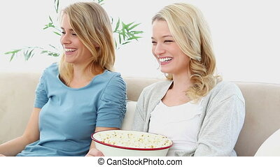 Two blonde women eating popcorn