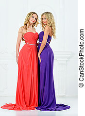 Two blonde women in evening dresses.