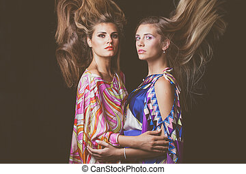 two blonde young women beauty fashion portrait with hair in motion
