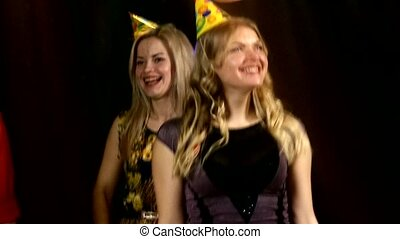 Two blondes in the foreground dancing a nightclub: birthday celebration