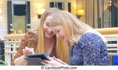 Two blondes sitting on a bench talking, bragging about their purchases Digital Tablet. CLose Up