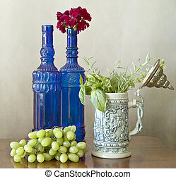 Two blue bottles, grapes and herbs - still life: two...