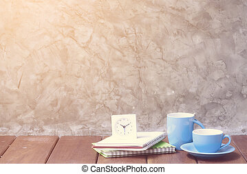 Two blue cups of coffee on wooden table with alarm clock and notebooks background, retro effect