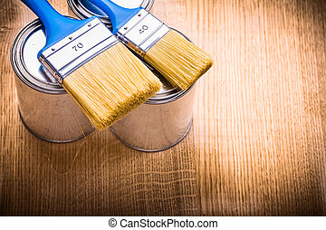 two blue paint brushes on cans and wooden board