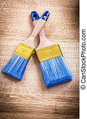 two blue paint brushes with wooden handles on vintage board