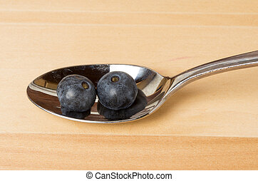 Two blueberries on a metal spoon