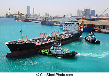 Two boats docked to industrial ship in port sail to sea at sunny day  in Abu Dhabi